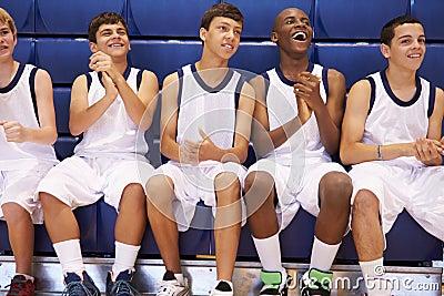 Members Of Male High School Basketball Team Watching Match