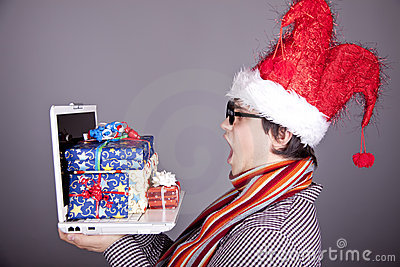 Men in christmas cap with gift boxes and notebook.