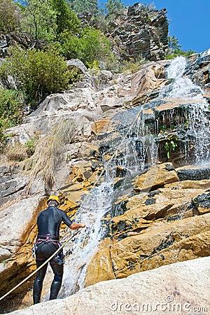 Men descending waterfall