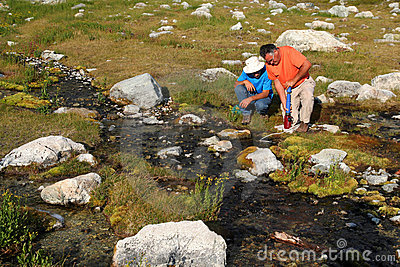 Men Filtering Water from Mountain Stream