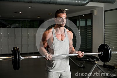 Men In The Gym Exercising Biceps With Barbell