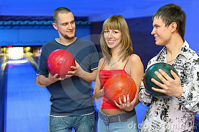 Men holds balls for bowling and look at girl