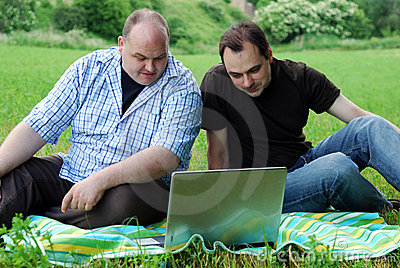 Men with laptops outdoors