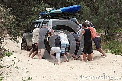Men pushing bogged car