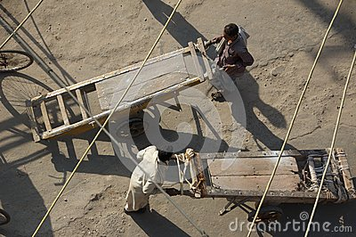 Men pushing wooden carts on dusty market square - Stock photo Editorial Photography
