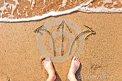 Mens bare feet in sand and arrows