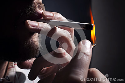 Men s hand lights cigarette with a match