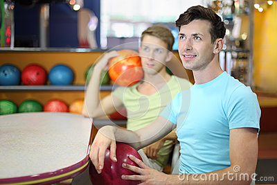 Men sit at table in bowling, hold balls