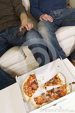Men Watching TV With Half Eaten Pizza On Table
