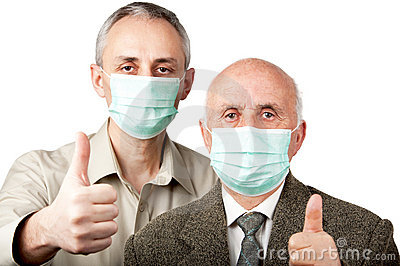 Men wearing flu masks and showing thumbs up