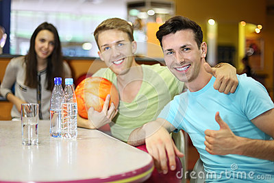 Men and woman with balls sit at table in bowling
