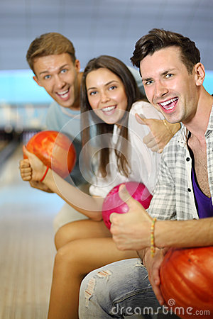 Men and woman hold balls, thumb up in bowling club