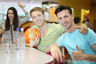 Men and woman sit at table in bowling