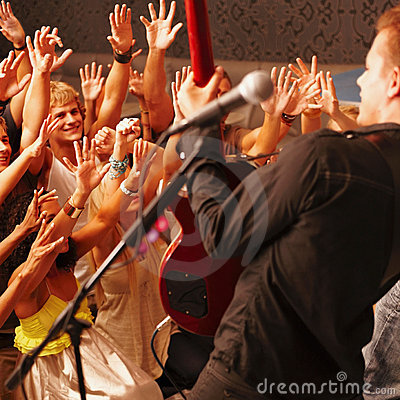 Men and women cheering a young guitarist