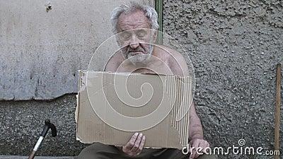 Mendiant assis dans la rue avec une pancarte vierge banque de vidéos