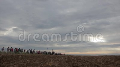 Menigte die op horizont door gebied lopen stock video