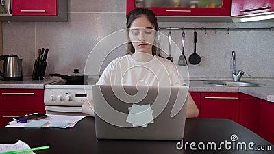 Menina abre laptop e trabalha na cozinha em casa video estoque