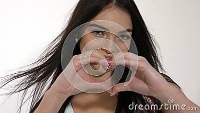 A menina adolescente de sorriso bonita faz a forma de um coração com suas mãos vídeos de arquivo