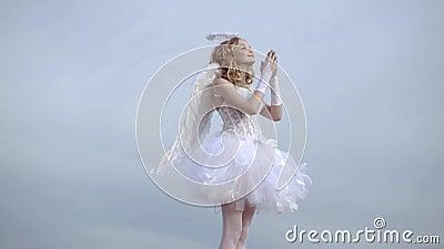 A menina adolescente feliz do anjo reza Crian?a com car?ter ang?lico Menina vestida como um anjo em um fundo claro do céu video estoque
