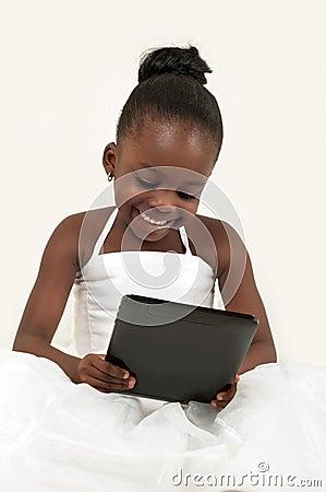 Menina afro-americano pequena que usa uma tabuleta digital