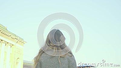 A menina alegre anda em uma rua da cidade com uma construção barroco no fundo no slo-mo filme