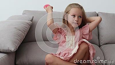 Menina alegre de seis anos de idade com um vestido cor-de-rosa senta-se num sofá e escova o cabelo louro vídeos de arquivo