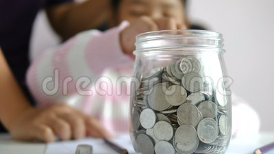 Menina asiática colocando a moeda no mealheiro e sorrindo com felicidade por dinheiro poupando para a riqueza no futuro da educaç video estoque