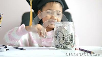 Menina asiática colocando a moeda no mealheiro e sorrindo com felicidade por dinheiro poupando para a riqueza no futuro da educaç filme