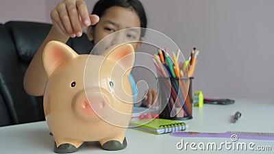 Menina asiática a colocar moeda na metáfora do banco porquinho, poupando dinheiro para um futuro melhor selecione foco profundida filme