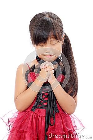 Menina asiática pequena que praying