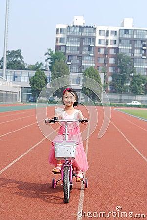 Menina asiática que monta uma bicicleta