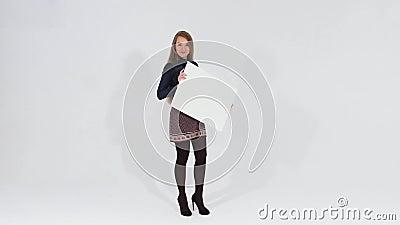 Menina atrativa de sorriso no vestido marrom que anda e que olha a câmera que guarda uma bandeira vazia branca filme