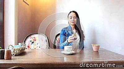 A menina bebe o chá ou o café, e prefere-os então escolher um vidro do vinho vídeos de arquivo