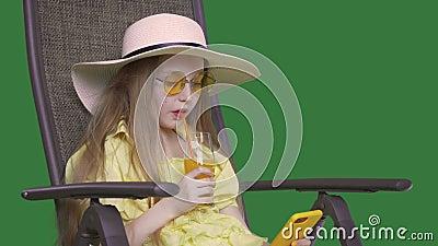 Menina bebendo suco de laranja e parecendo smartphone no dia de verão Menina sentada em cadeira e aproveitando coquetel de fruta filme