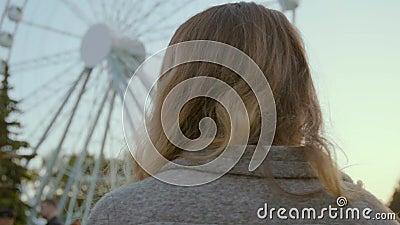 A menina bonita anda ao longo do parque da atração em um revestimento pastel à moda video estoque