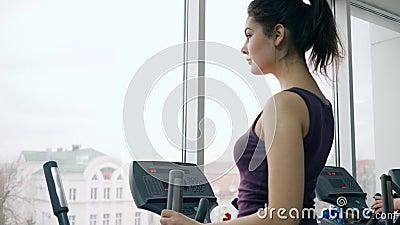 Menina bonita da aptidão que exercita no simulador no gym filme