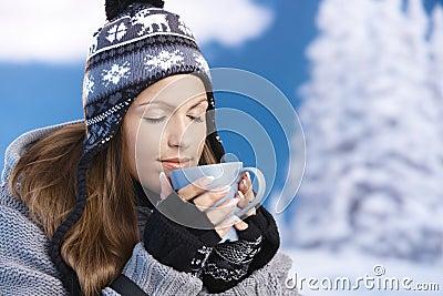 Menina bonita que bebe o chá quente nos olhos do inverno fechados
