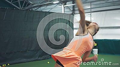Menina bonita que pratica servindo a bola no tênis vídeos de arquivo