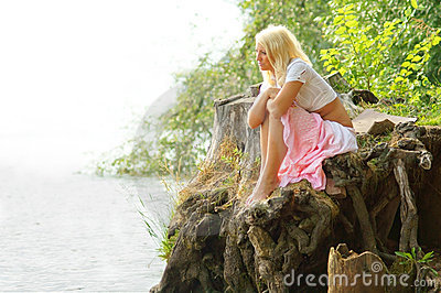 Menina bonita que senta-se na costa e que olha afastado