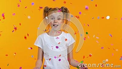 A menina bonito ? surpreendida que v? a queda dos confetes do c?u, celebra??o, inf?ncia filme