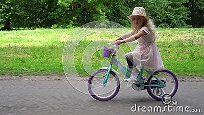 Menina bonito de sorriso que dá um ciclo no parque Tiro do movimento da paralela da suspensão Cardan filme
