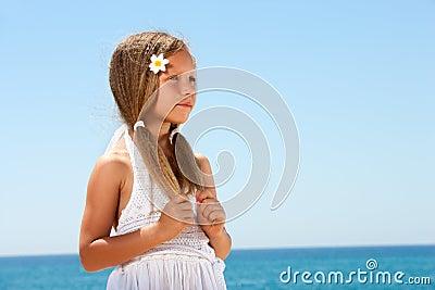 Menina bonito em olhar fixamente da praia.