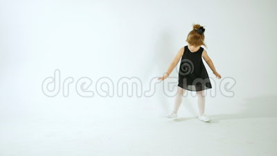 Menina bonito na dança preta do vestido e no divertimento ter, isolados no branco filme