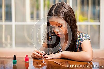 Menina bonito que usa o verniz para as unhas