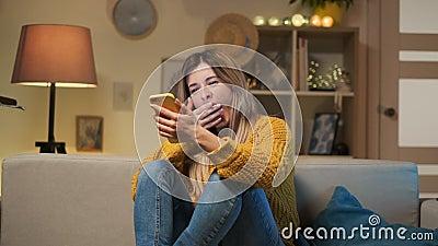 Menina cansado que senta-se no sofá com telefone celular, mensagem texting Mulher furada que boceja perto do smartphone em casa q video estoque