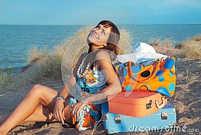Menina com as malas de viagem no mar