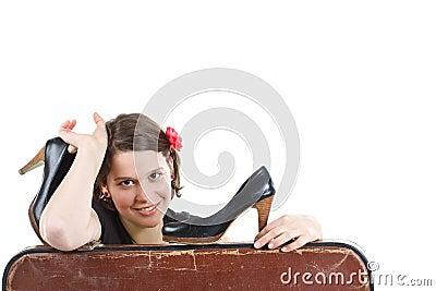 Menina com as sapatas nas mãos atrás da mala de viagem