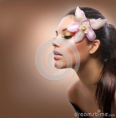 Menina com flor da orquídea