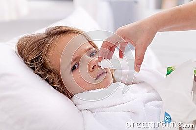 Menina com frio ruim usando o pulverizador nasal