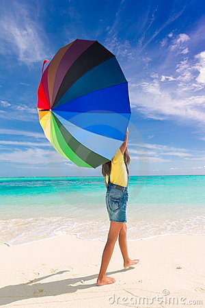 Menina com o guarda-chuva na praia